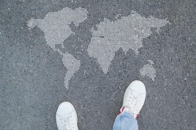 Mens in schoenen die zich in asfalt en wereldkaart bevinden.