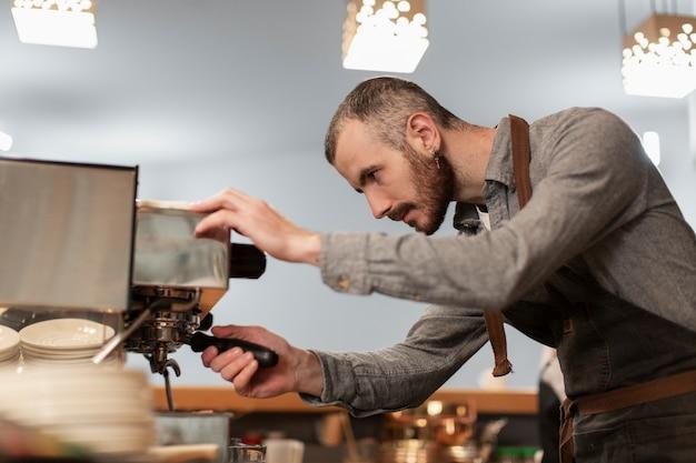 Mens in schort die aan koffiemachine werkt