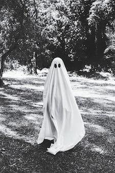 Mens in spookkostuum die zich in bos bevinden