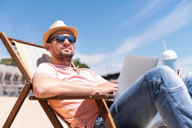 Mens in strandstoel die met laptop werkt