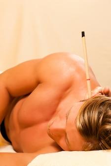 Mens in therapie met oorkaarsen