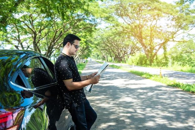 Mens in toevallige kleding die zich openluchthelling op zwarte sedanauto bevinden en letten op kaart na verloren manier