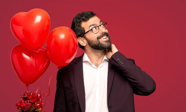 Mens in valentijnskaartdag die een idee denken terwijl het krassen van hoofd over rode achtergrond