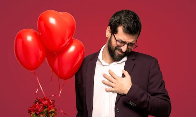 Mens in valentijnskaartdag die een pijn in het hart over rode achtergrond hebben