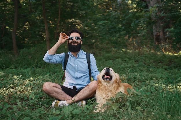 Mens in vrijetijdskleding en zijn hond stellen die aan camera kijken