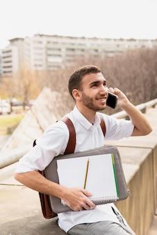 Mens in wit op telefoon spreekt en overhemd dat omhoog kijkt