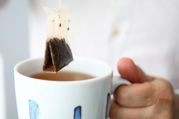 Mens in wit overhemd die de traditionele gezonde thee van ceylon in kop bewegen