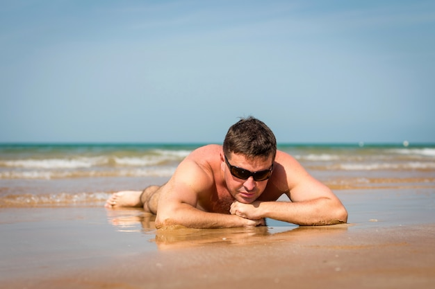 Mens in zonnebril die op het strand op overzeese achtergrond liggen