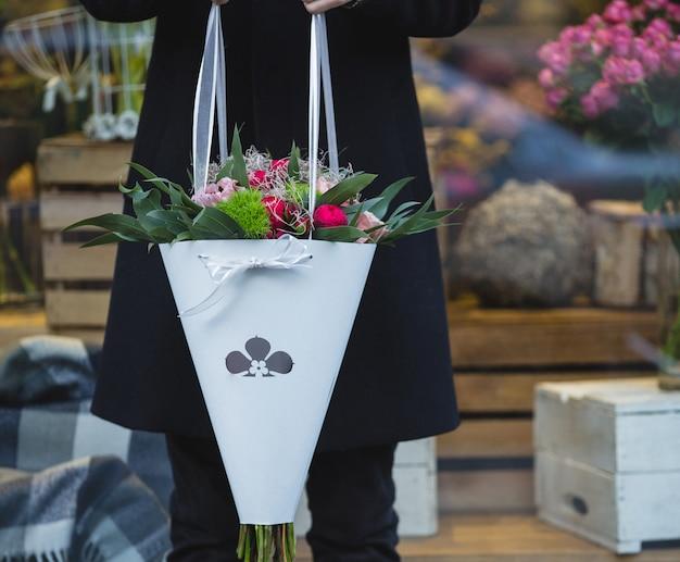 Mens in zwarte holing een witboekboeket van gemengde bloemen.