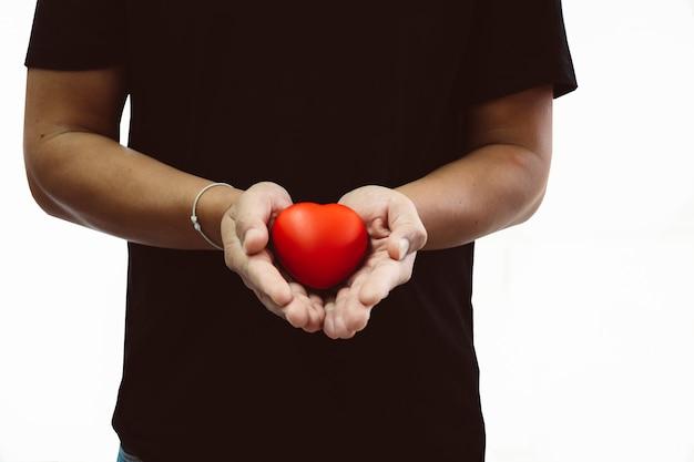 Mens in zwarte t-shirt die rood hart in zijn hand houdt