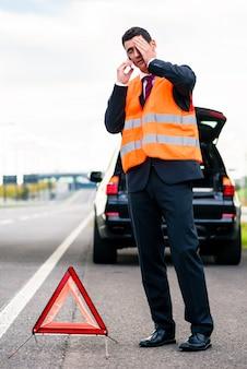 Mens met autoanalyse die gevarendriehoek opricht
