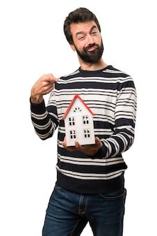 Mens met baard die een klein huis houdt