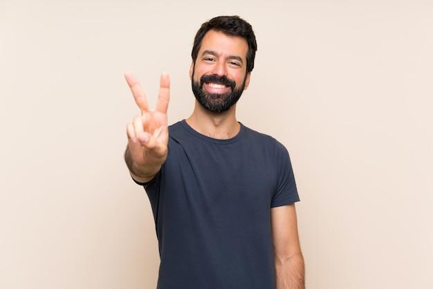 Mens met baard die en overwinningsteken glimlachen tonen