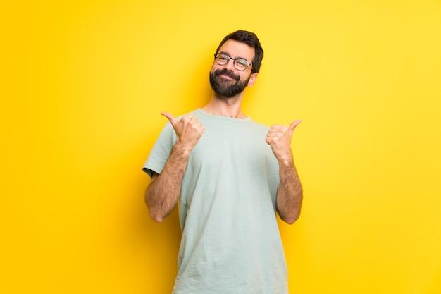Mens met baard en groen overhemd die duimen op gebaar met beide handen en het glimlachen geven