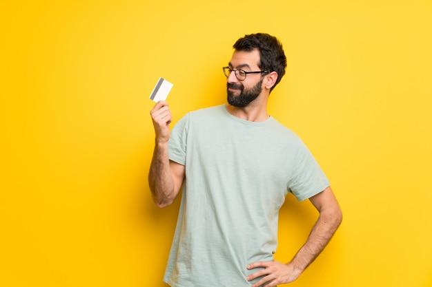 Mens met baard en groen overhemd die een creditcard en het denken houden