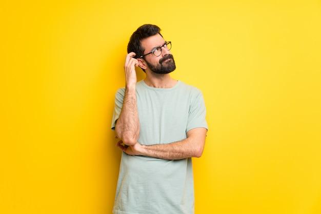 Mens met baard en groen overhemd die twijfels hebben terwijl hoofd krassen