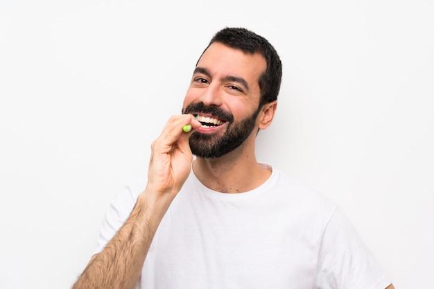 Mens met baard het borstelen tanden over geïsoleerd wit