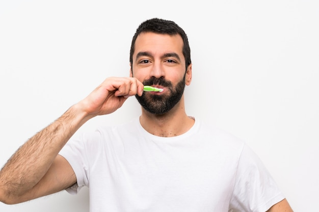 Mens met baard het borstelen tanden over geïsoleerde witte muur