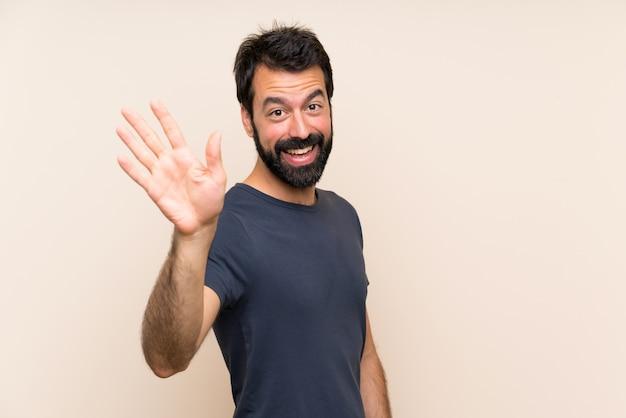 Mens met baard het groeten met hand met gelukkige uitdrukking