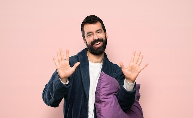 Mens met baard in pyjama's die tien met vingers over geïsoleerde roze achtergrond tellen