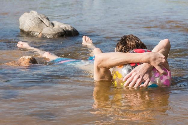 Mens met bal die in water ligt