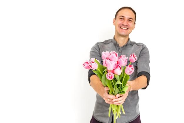 Mens met bloemen. romantische man met boeket tulpen voor verjaardag. fijne vrouwendag. het geven van boeket bloemen. knappe man die bloemen geeft. witte achtergrond. horizontale foto.s