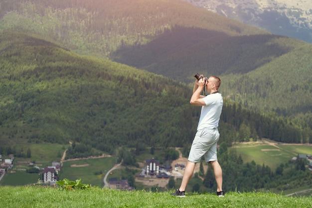Mens met camera die zich op heuvel bevindt
