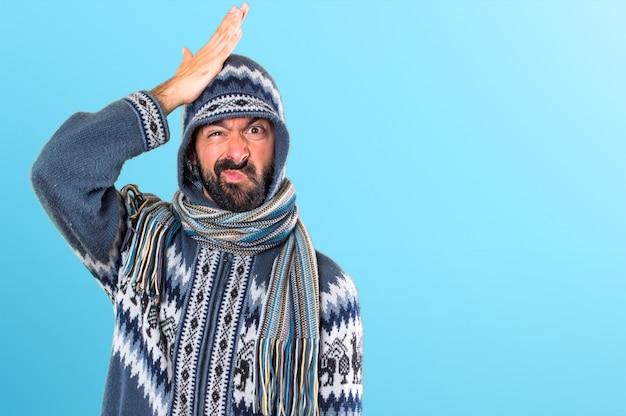 Mens met de winterkleren die twijfels op kleurrijke achtergrond hebben