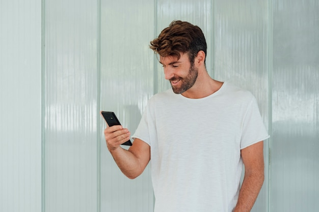 Mens met de witte telefoon van de t-shirtholding