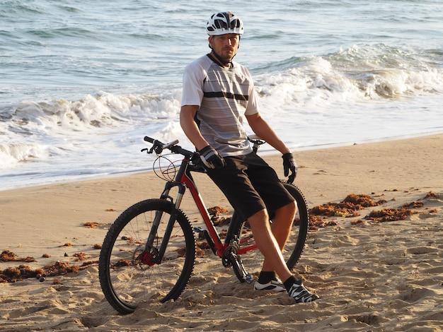 Mens met een fiets die op het strand rust