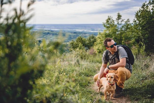 Mens met een hond die bij de wandelingssleep rust