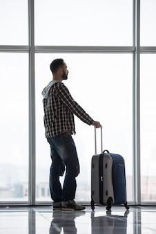Mens met een koffer die op zijn vlucht wacht.