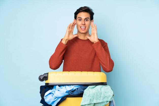 Mens met een kofferhoogtepunt van kleren over geïsoleerde blauwe muur die met wijd open mond schreeuwen