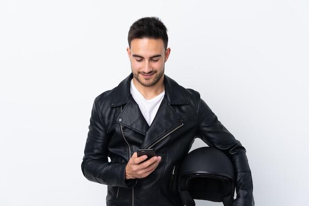 Mens met een motorhelm die een bericht met mobiel verzendt