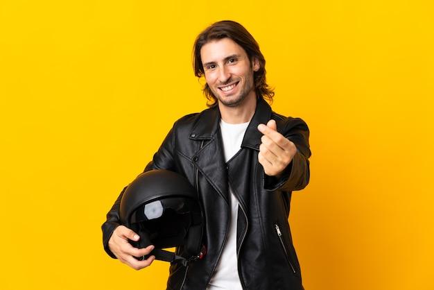 Mens met een motorhelm die op gele muur wordt geïsoleerd die geldgebaar maakt