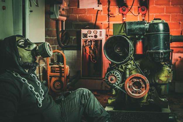 Mens met gasmasker en een hamer in machinekamer. concept van nucleaire, biologische en chemische gevaren.