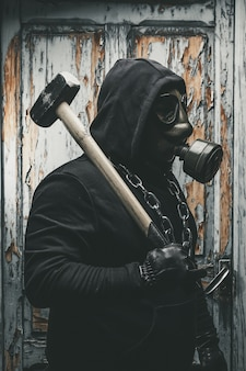 Mens met gasmasker en een hamer in machinekamer. concept van nucleaire, biologische en chemische gevaren. Premium Foto