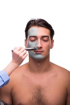Mens met gezichtsmasker dat op wit wordt toegepast
