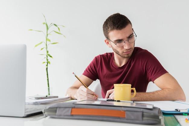 Mens met glazen wordt geconcentreerd wit lezend een document