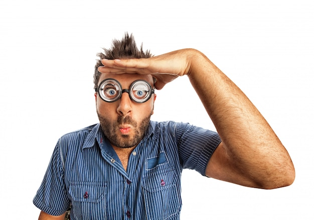 Mens met grappige uitdrukking en dikke glazen ver weg kijkend.