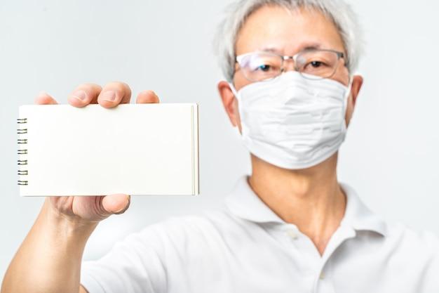Mens met grijs haar die medisch masker dragen en blanco document blocnote houden