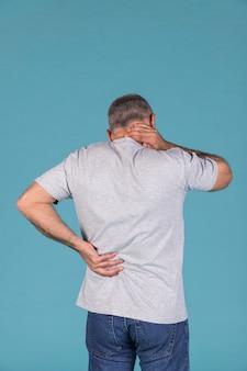 Mens met hals en rugpijn die zich voor blauwe achtergrond bevinden