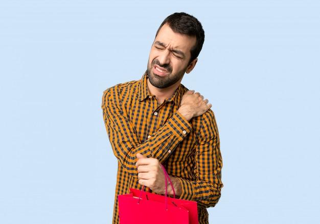 Mens met het winkelen zakken die aan pijn in schouder lijden voor een inspanning op geïsoleerde blauwe achtergrond te hebben gemaakt