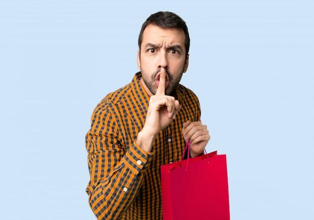 Mens met het winkelen zakken die een teken van stiltegebaar tonen die vinger in mond op geïsoleerde blauwe achtergrond zetten