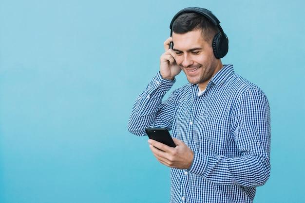 Mens met hoofdtelefoons en smartphone in stedelijk milieu