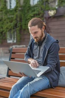 Mens met hoofdtelefoons in de stad die aan laptop werkt