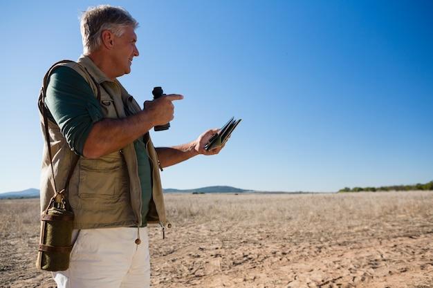 Mens met kaart en verrekijker die weg op landschap kijken