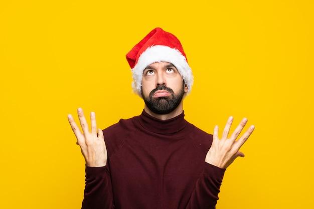 Mens met kerstmishoed over geïsoleerde gele achtergrond die door een slechte situatie wordt gefrustreerd