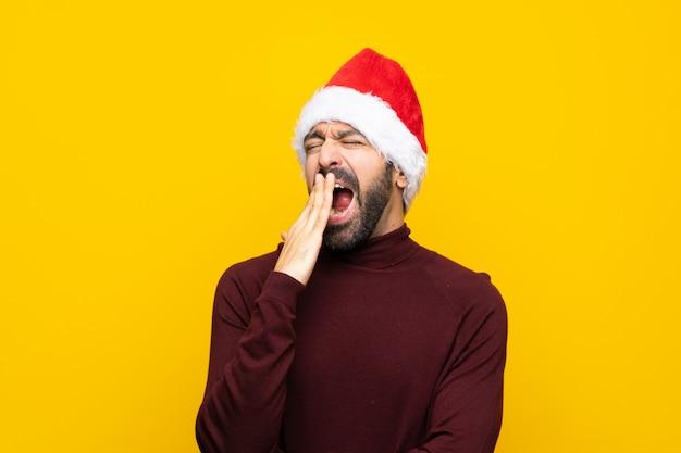 Mens met kerstmishoed over geïsoleerde gele muur die en wijd open mond geeuwen behandelen met hand