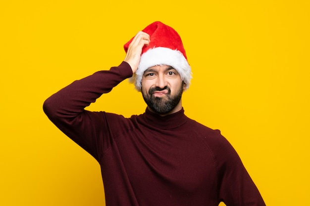 Mens met kerstmishoed over geïsoleerde gele muur met een uitdrukking van frustratie en niet begrip